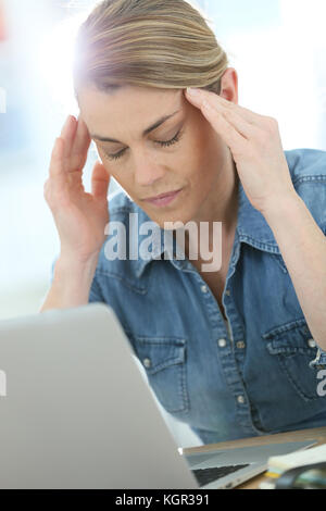 Woman in front of laptop suffering headache - Stock Photo