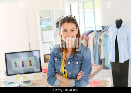 Portrait of smiling fashion designer in studio - Stock Photo