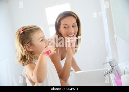 Mother and daughter in bathroom brushing her teeth - Stock Photo