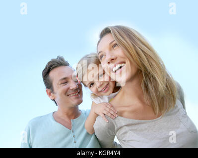 Parents giving piggyback ride to little girl, sunny day - Stock Photo