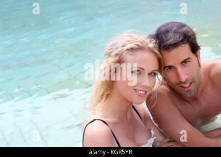 Portrait of couple in resort swimming pool - Stock Photo