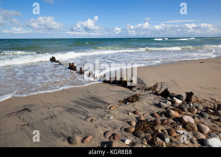 Old wooden posts and pebbles on sand beach with breaking waves and cumulus clouds, Rageleje, Kattegat Coast, Zealand, - Stock Photo