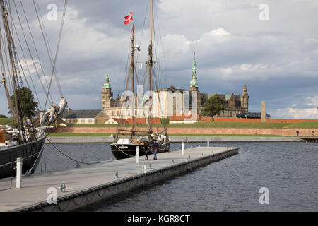 Tall ship in harbour with Kronborg Castle used as setting for Shakespeare's Hamlet in distance, Helsingor, Zealand, - Stock Photo