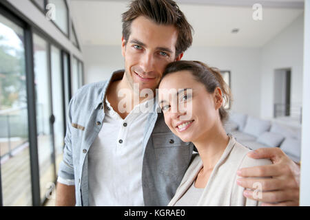 Portrait of smiling couple relaxing at home - Stock Photo