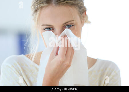 Young woman with cold blowing her runny nose - Stock Photo