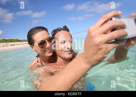 Couple in Caribbean sea taking picture of themselves - Stock Photo