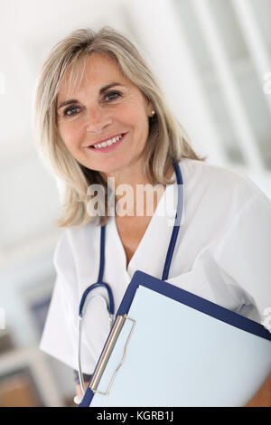 Portrait of smiling senior nurse in hospital - Stock Photo
