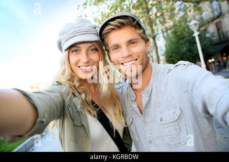 Cheerful trendy couple taking self-portrait picture - Stock Photo