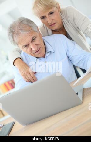 Senior couple doing the income tax declaration online - Stock Photo