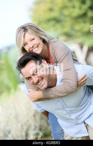 Cheerful mature man giving piggyback ride to woman - Stock Photo