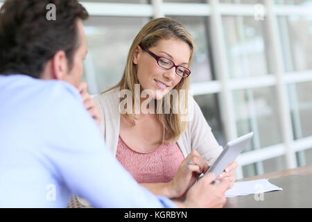 Businesswoman in business meeting using tablet - Stock Photo