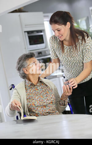 Portrait of elderly woman in wheelchair with home carer - Stock Photo