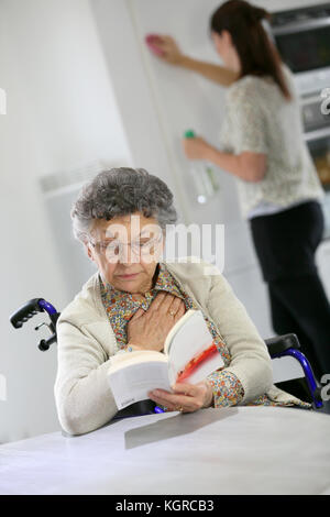 Elderly woman reading book, home helper in background - Stock Photo