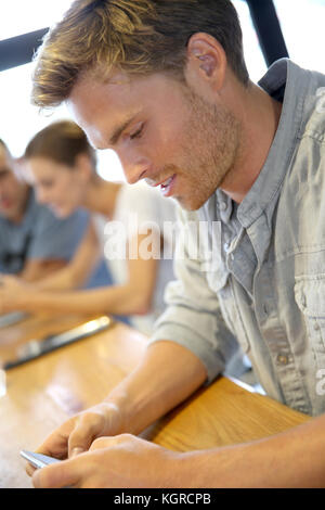 Young man sending message with smartphone - Stock Photo
