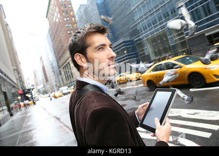 Businessman in Manhattan using digital tablet in the street - Stock Photo