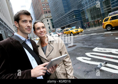 Business people using tablet in the street of Manhattan - Stock Photo