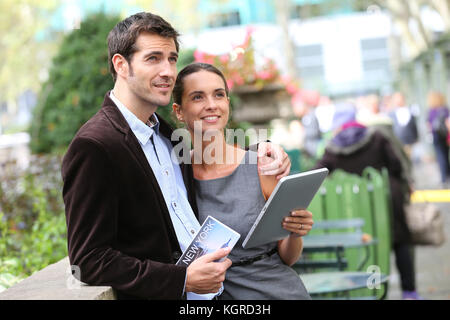 Couple of tourists in Bryant Park using tablet and city guide - Stock Photo