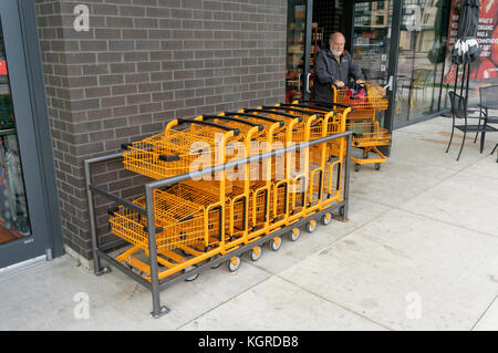 Elderly man pushing an orange metal wire shopping cart outside a store in Vancouver, BC, Canada - Stock Photo