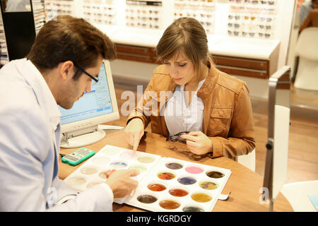 Woman with optician choosing spectacle lenses colour - Stock Photo