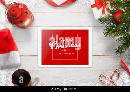 Merry Christmas greeting card with tablet, Christmas tree, gifts and decorations. Top view with white wooden desk - Stock Photo