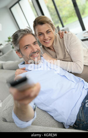 Lovers Watching Tv In The Living Room At Home Stock Photo