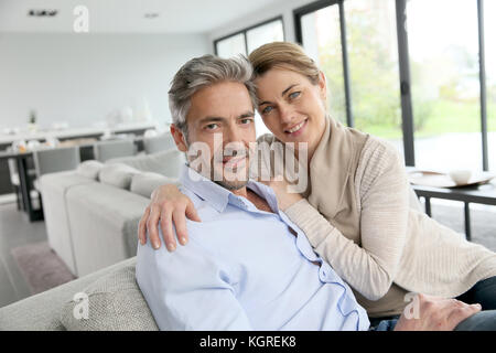 Portrait of 45-year-old couple relaxing in modern house - Stock Photo