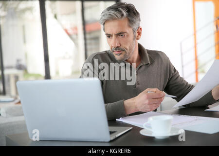 Mature man calculating budget on laptop - Stock Photo