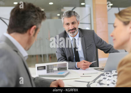 Architect meeting with clients in office - Stock Photo