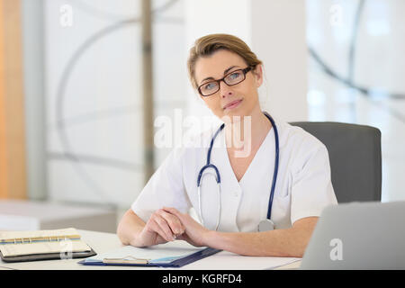 Portrait of mature nurse sitting at desk in office - Stock Photo