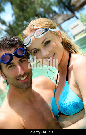 Portrait of couple in pool with goggles - Stock Photo