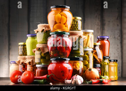 Jars with variety of pickled vegetables. Preserved food - Stock Photo