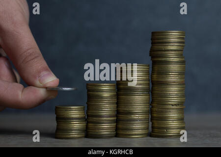 Closeup of hand put Coins to stack of coins,Concept Saving money. - Stock Photo
