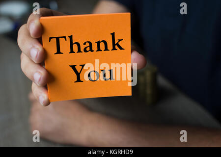 Hand holding an orange Paper with the word thank you  - Business Concept - Stock Photo