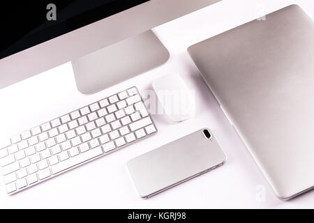 Modern workplace with metallic pc with keyboard and mouse, mobile phone, metalic laptop lying on a desk isolated - Stock Photo