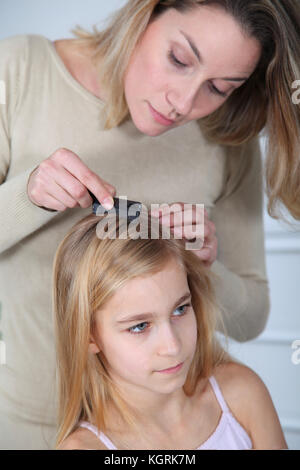 Mother treating daughter's hair against lice - Stock Photo