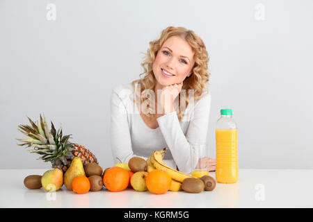 Smiling blond woman sitting with fruits on table - Stock Photo