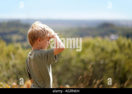 A little 8 year old boy out on a nature hike, is sheilding his eyes from the sun as he looks out over the trees - Stock Photo