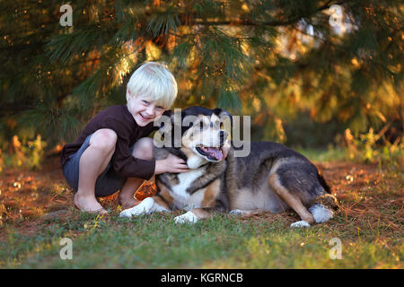 A cute, and happy smiling 5 year old little child is hugging his mix breed German Shepherd Dog, outside under the - Stock Photo