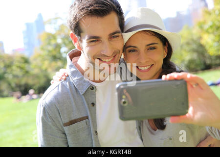 Cheerful couple taking picture of themselves in central park - Stock Photo