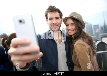 Couple taking picture with smartphone, skyline in background - Stock Photo