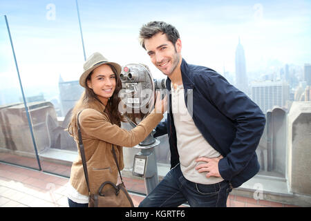 Tourists looking through telescope on Top of the Rock building - Stock Photo