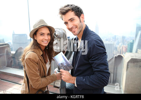 Couple on Top of the Rock observation desk with city guide - Stock Photo
