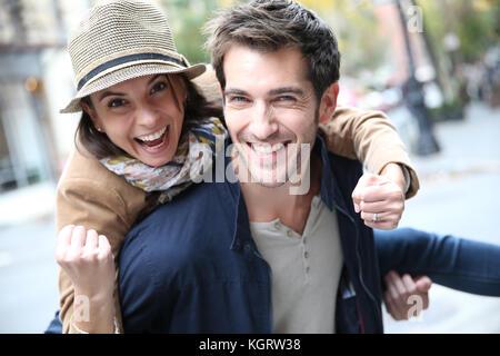 Man giving piggyback ride to girlfriend, having fun - Stock Photo