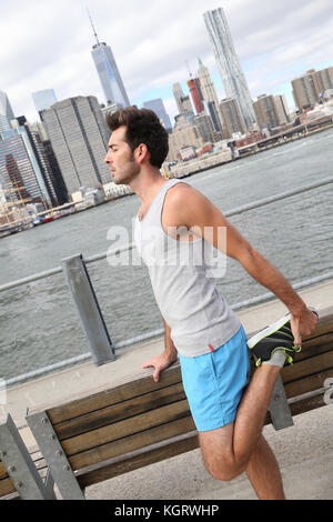 Man stretching out after training on Brooklyn Heights promenade - Stock Photo