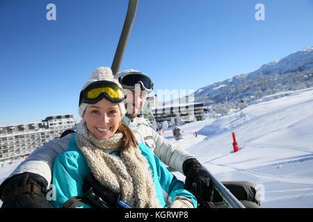 Couple sitting on ski resort chairlift - Stock Photo