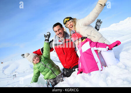 Cheerful family having good time in snowy mountain - Stock Photo