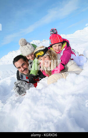 Portrait of happy family laying down in snow - Stock Photo