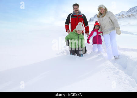 Family walking in deep snow track - Stock Photo