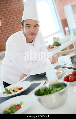 Portrait of chef in professional kitchen - Stock Photo