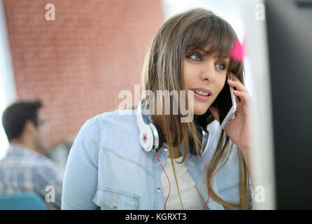 Young woman talking on smartphone in front of desktop - Stock Photo